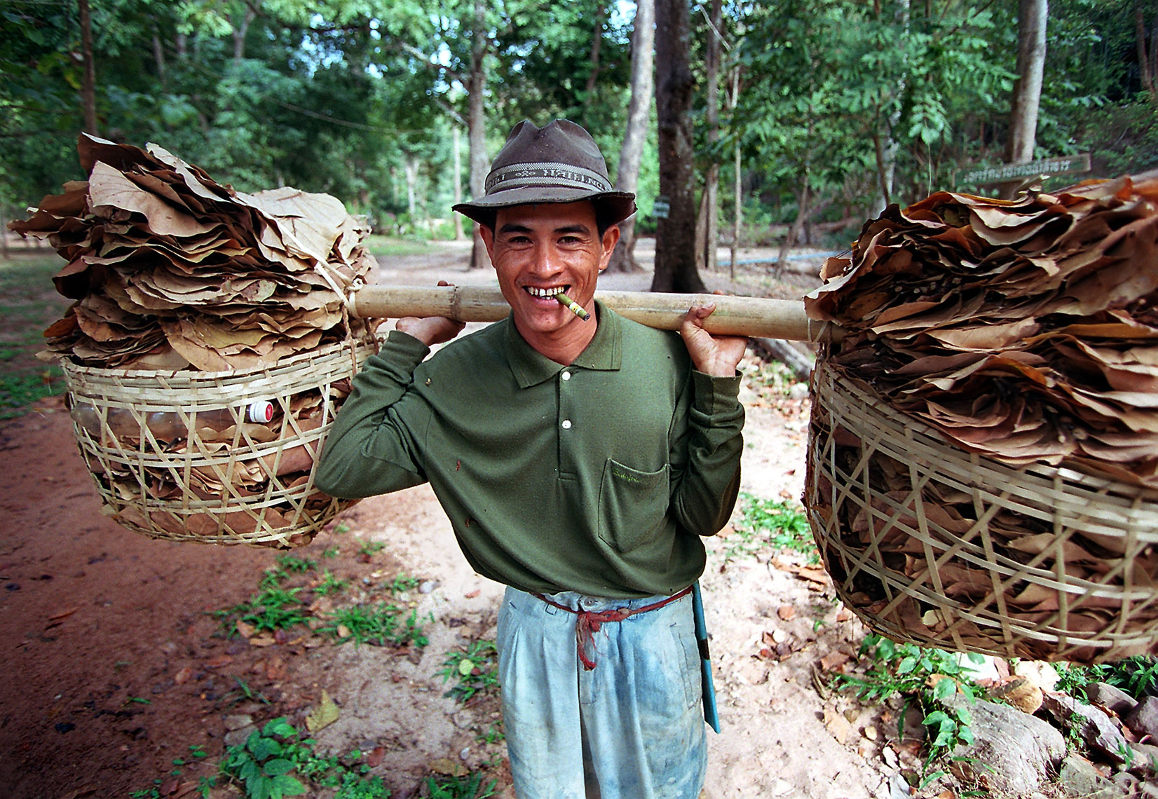 Thai-guy-with-baskets-of-leaves